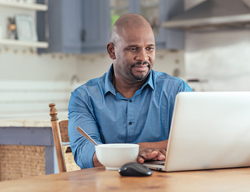 A black man studying at his kitchen table
